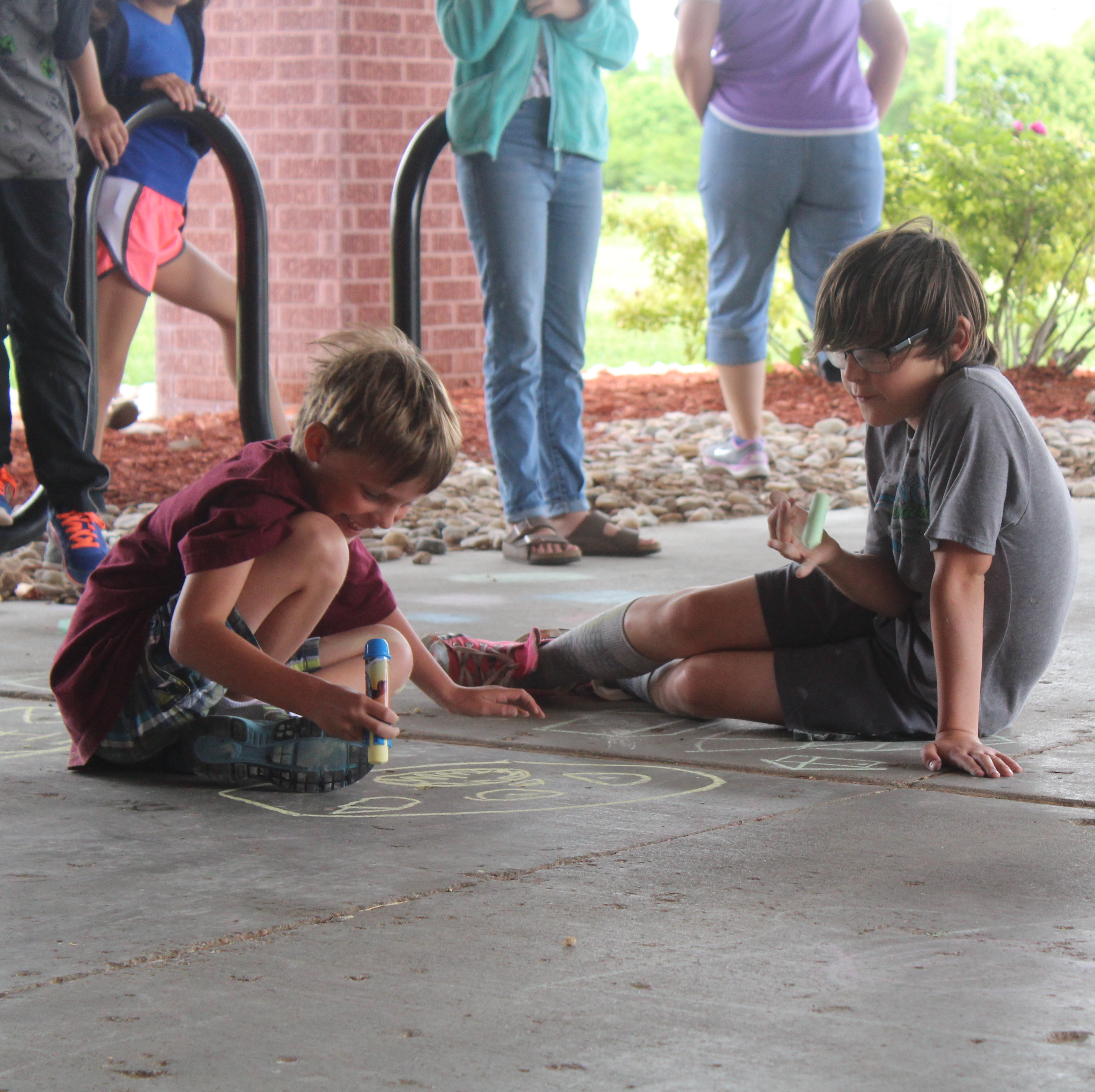 BCE kids camp photo of children drawing with chalk on concrete.